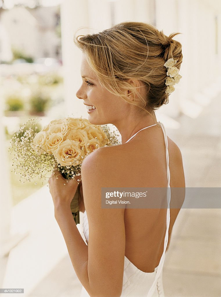 Side View of a Bride Holding a Bouquet of White Roses and Standing in a Colonnade : Stock Photo
