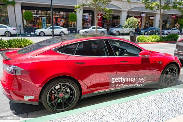 Side view of a bright red Tesla Model 3 automobile from Tesla Motors parked on the street at Santana Row a luxury outdoor shopping mall in the...