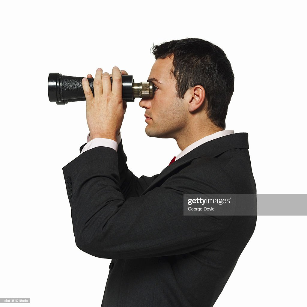 side view of a businessman looking through binoculars : Stock Photo