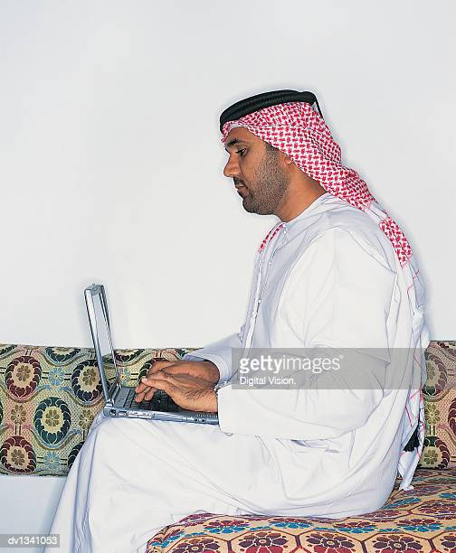 Side View of a Businessman Wearing Traditional Middle Eastern Dress and Using a Laptop on a Sofa