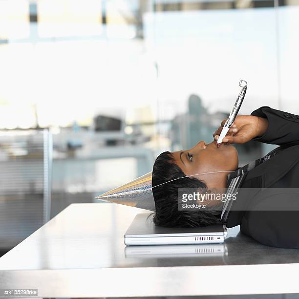 side view of a businesswoman wearing a party hat and blowing a whistle with her head resting on laptop