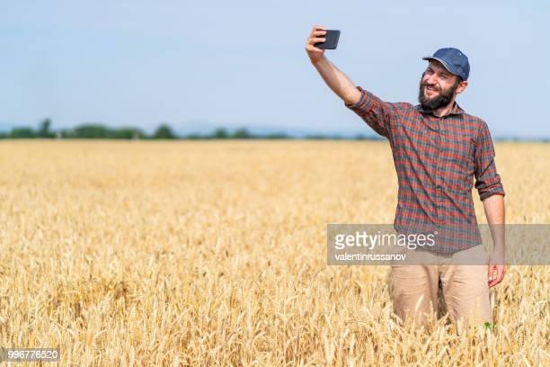 Vue latérale d'un agriculteur en utilisant le téléphone intelligent et une selfie dans le domaine