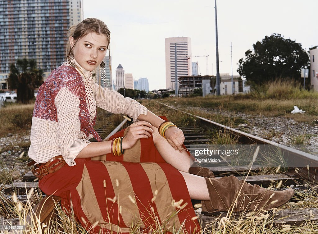 Side View of a Fashionable Woman Sitting on Urban Railway Tracks : Stock Photo
