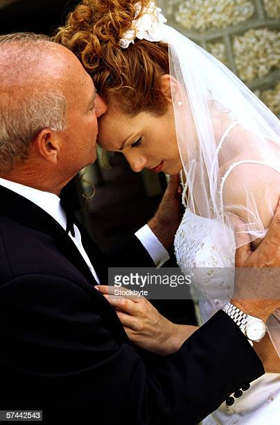 side view of a father kissing her daughter in her wedding gown