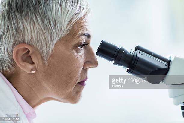 Side view of a female scientist looking through a microscope.