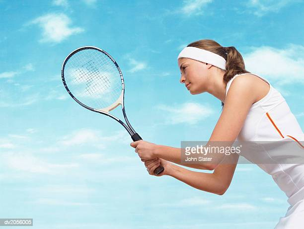 Side View of a Female Tennis Player Holding a Tennis Racket