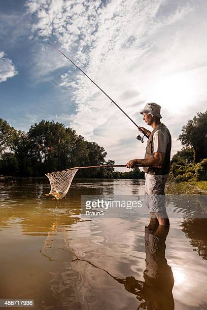 Side view of a fisherman holding his catch in net.