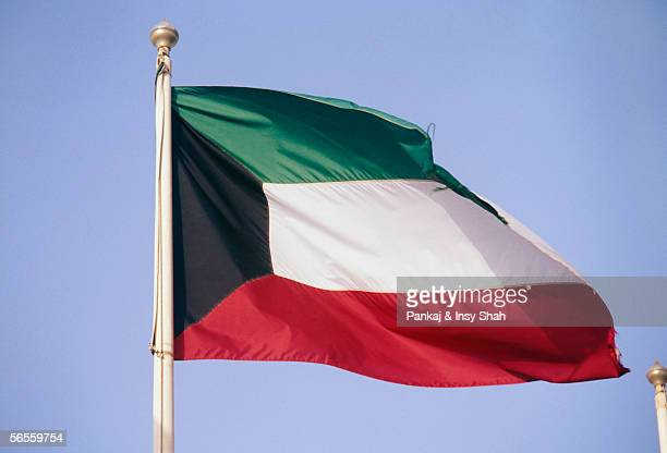 side view of a flag fluttering due to breeze. - kuwaiti flag stock pictures, royalty-free photos & images