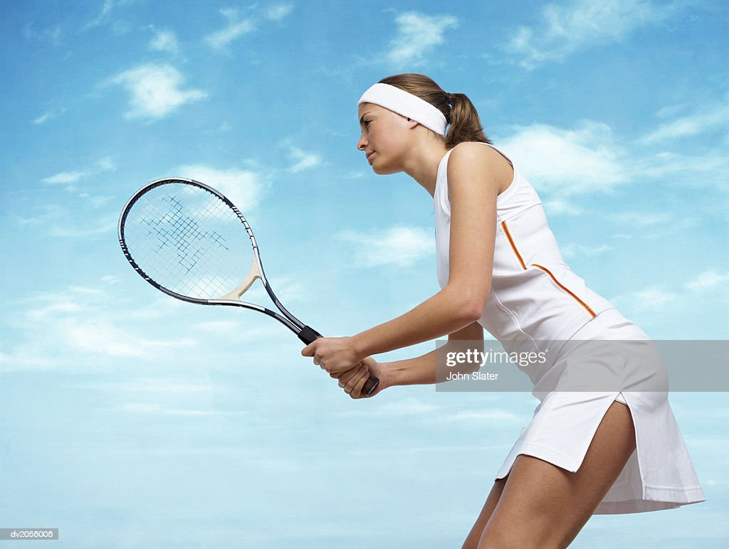 Side View of a Focused Female Tennis Player Holding a Tennis Racket : Stock Photo