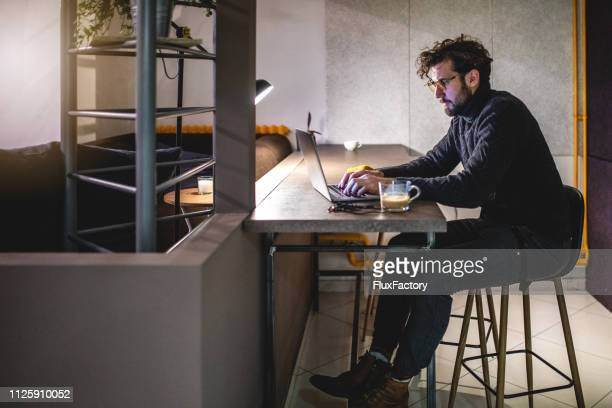 side view of a freelance designer working late at night - creative director stock pictures, royalty-free photos & images