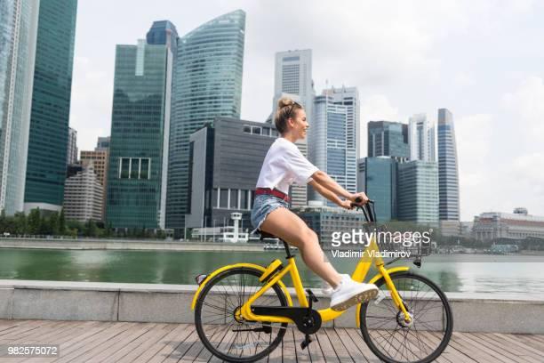vista lateral de uma rapariga a andar de bicicleta na cidade - amarelo - fotografias e filmes do acervo