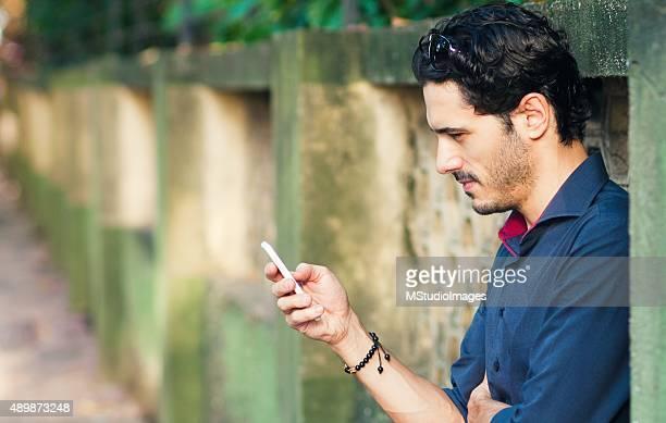 Vista lateral de um homem utiliza um smartphone
