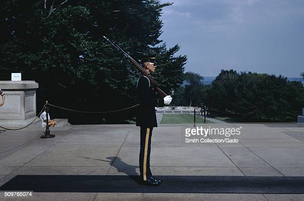 Side view of a lone soldier in uniform guarding The Tomb of the Unknowns standing in front of the entrance with trees and a green lawn in the...