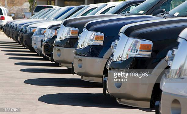 Side view of a long row of automobile front bumpers in a lot