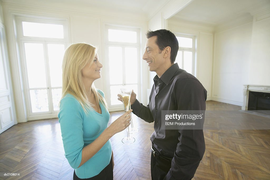 Side View of a Man and Woman Drinking Champagne in a Large Empty Room with a Wooden Floor : Stock Photo