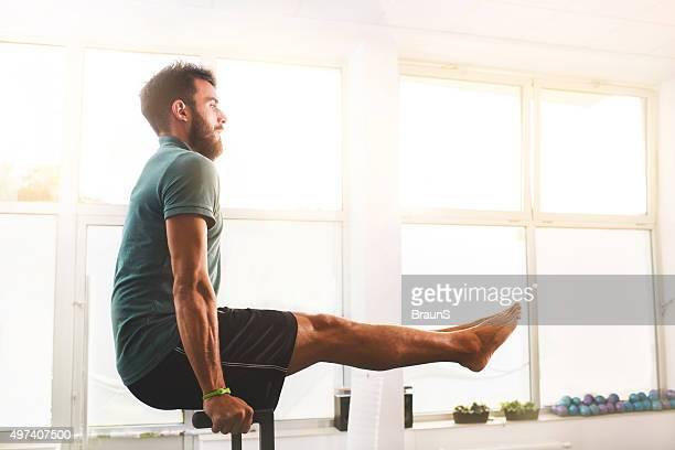 Vista lateral de un hombre haciendo ejercicios de Pilates equilibrio.