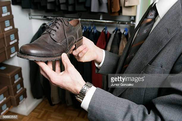 Side view of a man holding a shoe in his hands in a retail store