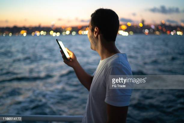 side view of a man making a video chat at a boat - nautical vessel stock pictures, royalty-free photos & images