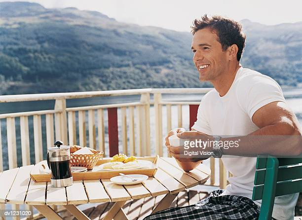 Side View of a Man Sitting at an Outdoor Breakfast Table Holding a Cup of Coffee
