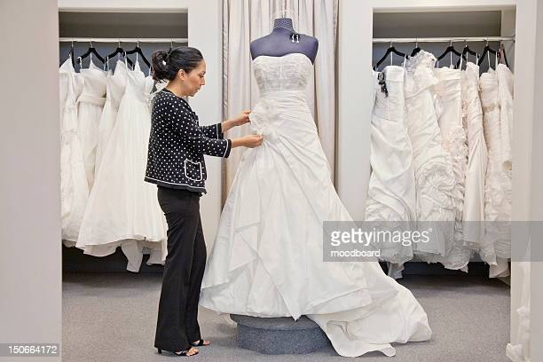 side view of a mature employee adjusting elegant wedding dress in bridal store - wedding dress stock pictures, royalty-free photos & images