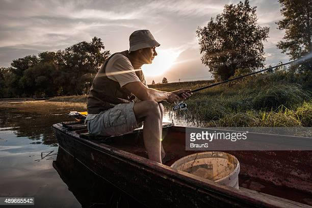 Side view of a pensive fisherman in boat at sunset.