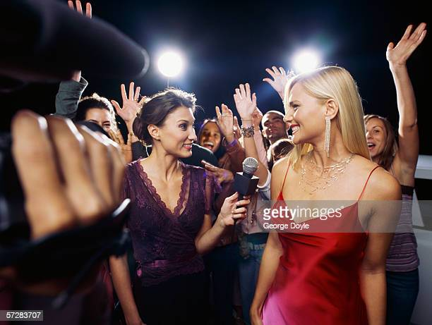 Side view of a presenter interviewing a star at ceremony award