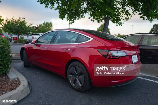Side view of a red Tesla Model 3 electric car from Tesla Motors under a dramatic sky in the San Francisco Bay Area Dublin California May 21 2018