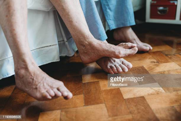 side view of a senior couple's feet on the side of bed - old man feet stock pictures, royalty-free photos & images