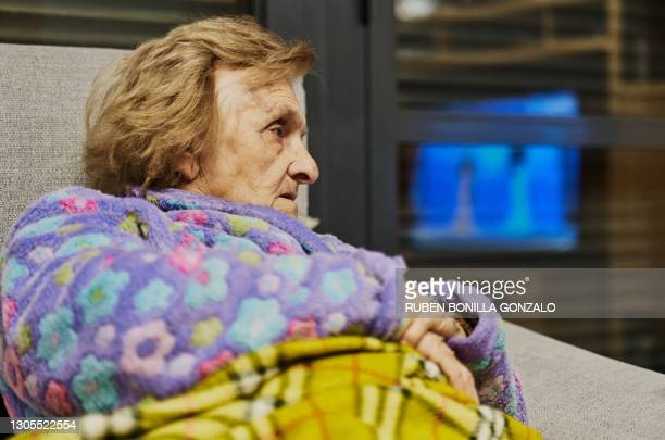 side view of a senior woman watching television screen. - film screening stock pictures, royalty-free photos & images