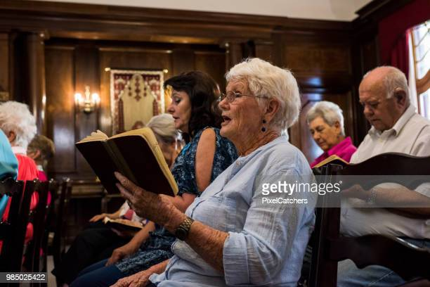 side view of a senior women singing in church - church stock pictures, royalty-free photos & images