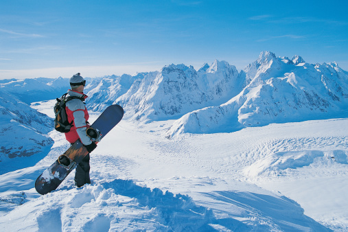 Side View of a Snowboarder Looking at the View of a Snow-covered Mountain Valley - gettyimageskorea