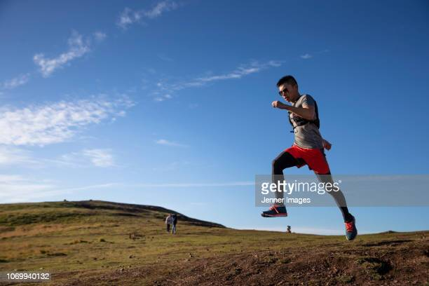 side view of a trail runner training in nature. - one man only stock pictures, royalty-free photos & images