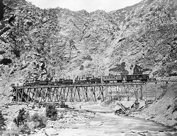 Side view of a train on the Devils Gate Bridge during the building of the Union Pacific Railroad America's first transcontinental railway
