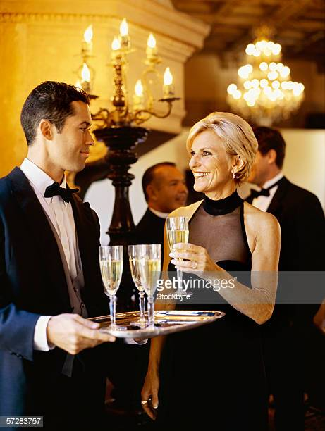 Side view of a waiter serving champagne to a mature woman