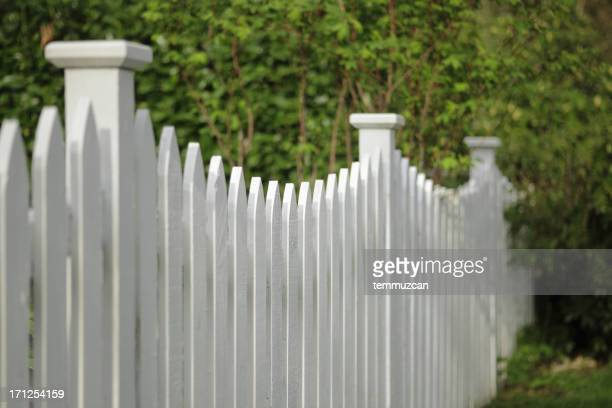 A side view of a white picket fence