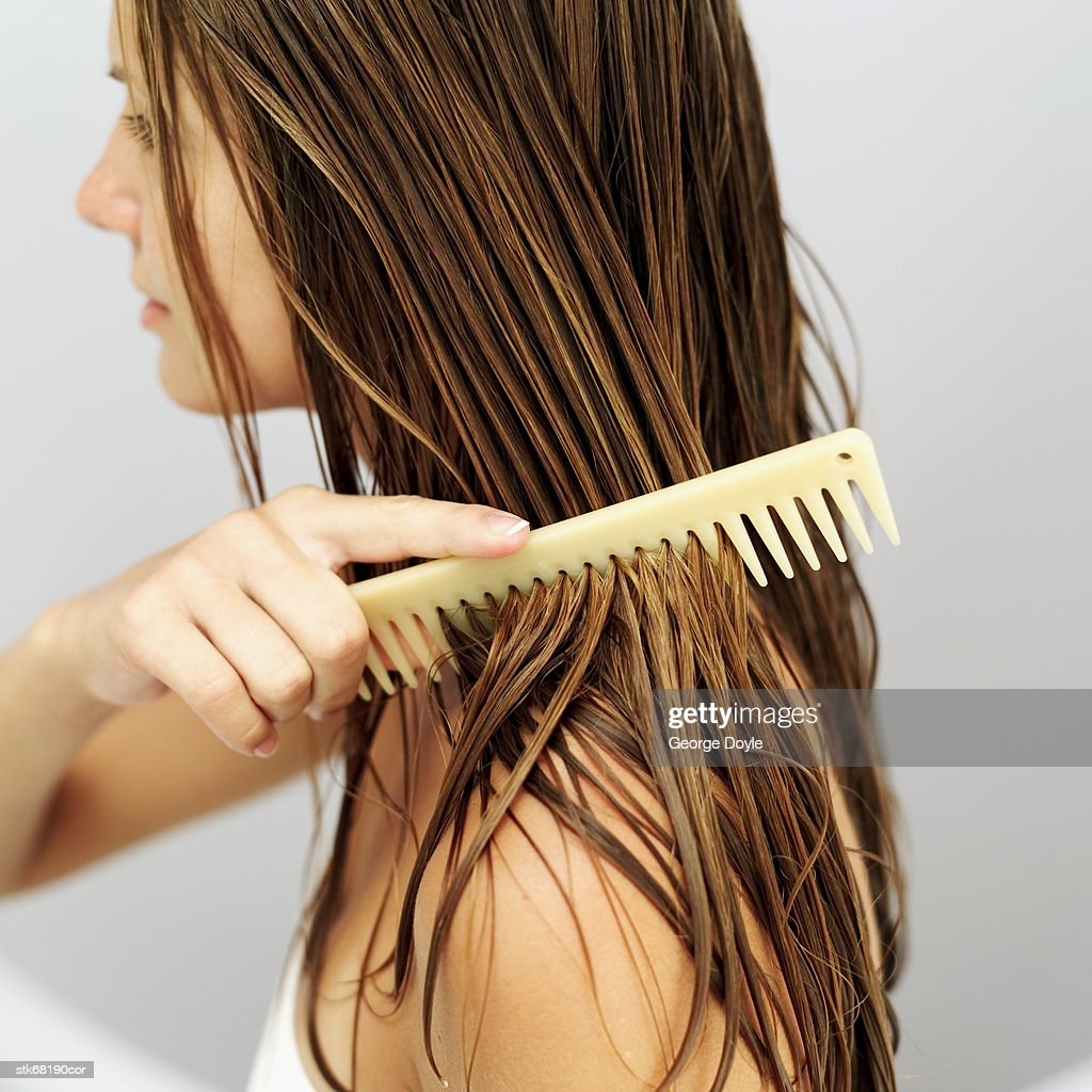 side view of a woman combing her hair : Stock Photo