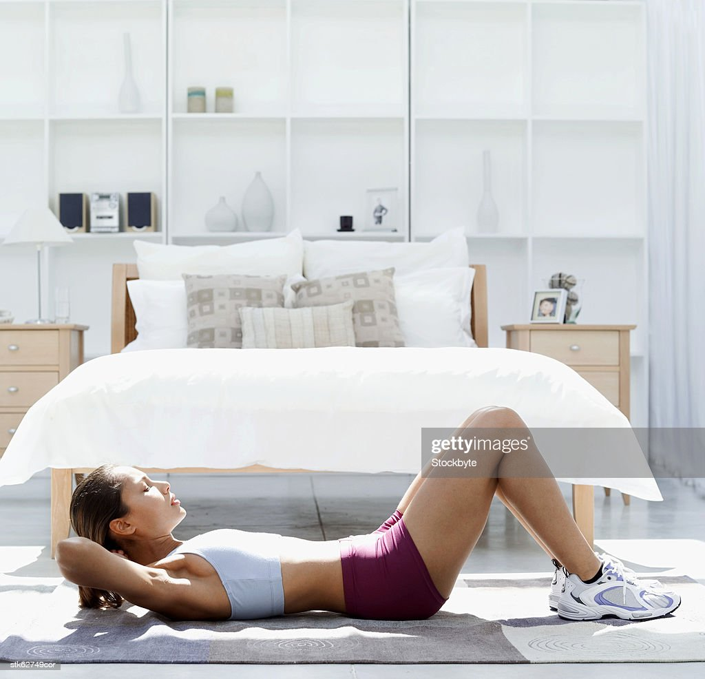 side view of a woman doing sit ups on the floor : Stock Photo