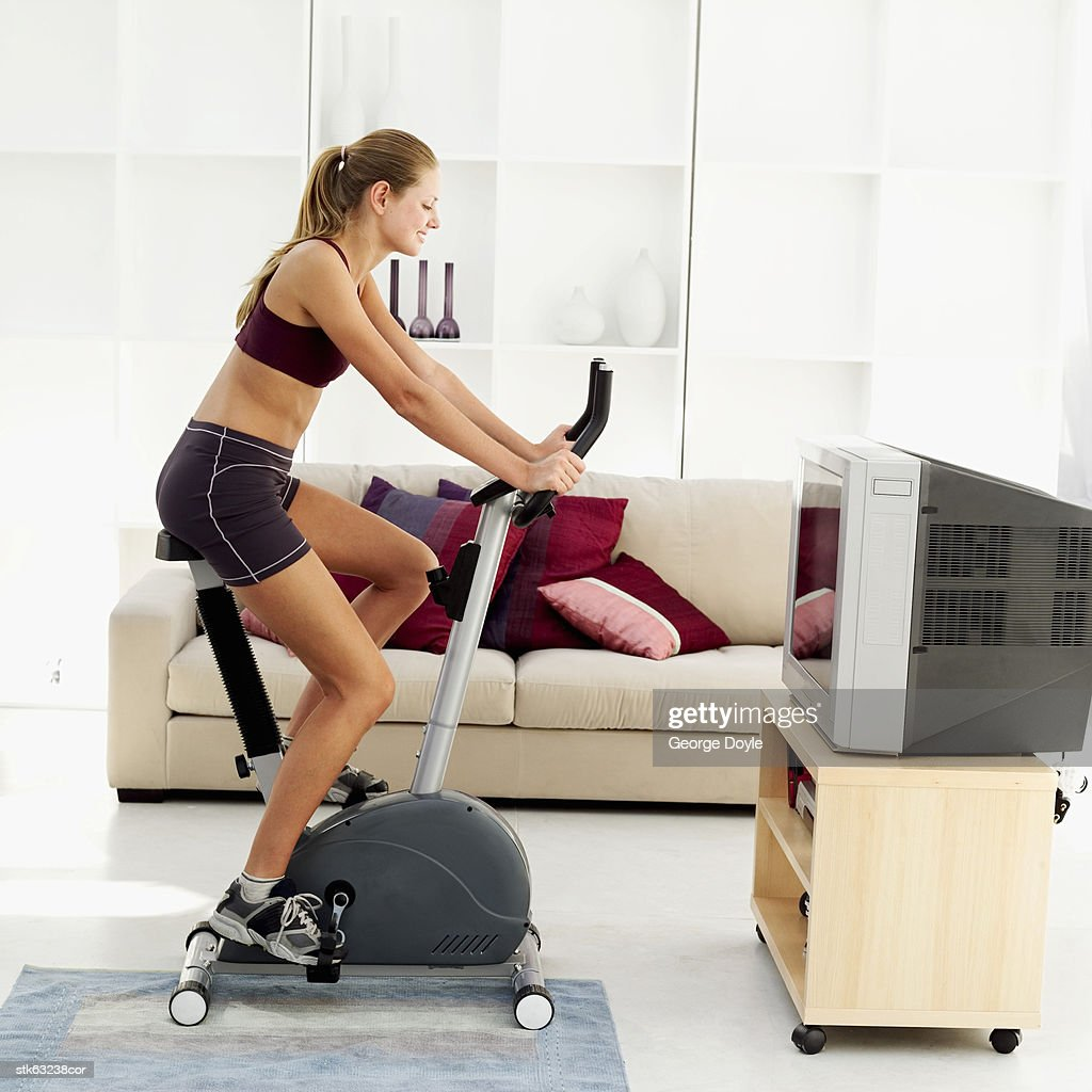 side view of a woman exercising on an exercise bicycle in her living room : Stock Photo