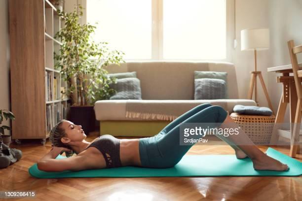 彼女のマットの上に自宅で練習スポーツウェアの女性のサイドビュー - 自重トレーニング ストックフォトと画像