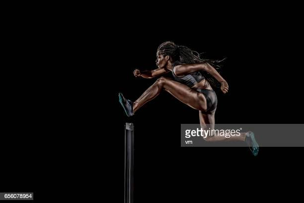 side view of a woman jumping over a hurdle - hurdling stock photos and pictures