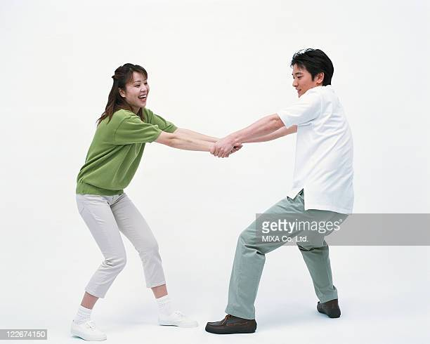 side view of a woman pulling her husband's hand - 引く ストックフォトと画像