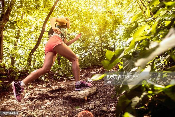 side view of a woman running uphill in a forest - cross country running stock pictures, royalty-free photos & images