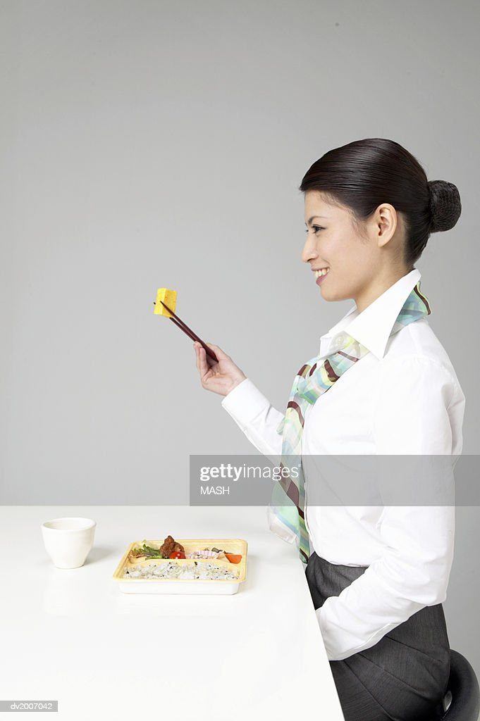 Side View of a Woman Sitting at a Table Eating Food With Chopsticks : Stock Photo