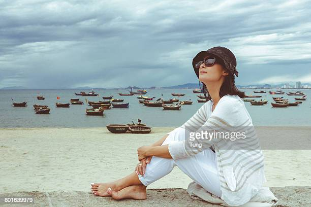 Side view of a woman sitting on wall by the beach, My Khe, Danang City, Vietnam