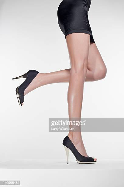side view of a woman standing on one leg, waist down - talons aiguilles photos et images de collection