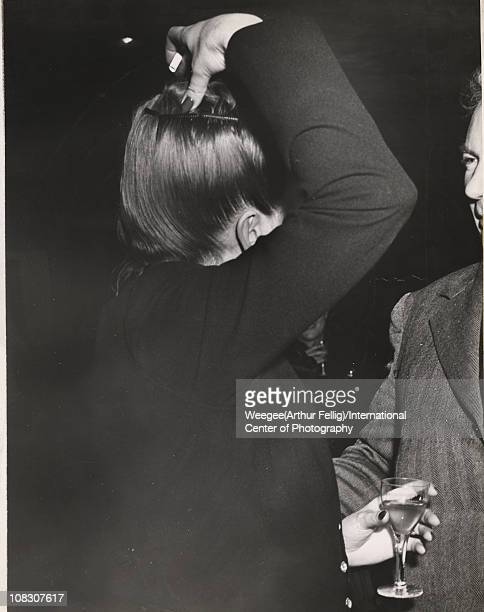 Side view of a woman touching the top of her head with one hand and holding a drink with the other perhaps at an opening reception of an art or...