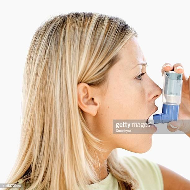 side view of a woman using an inhaler