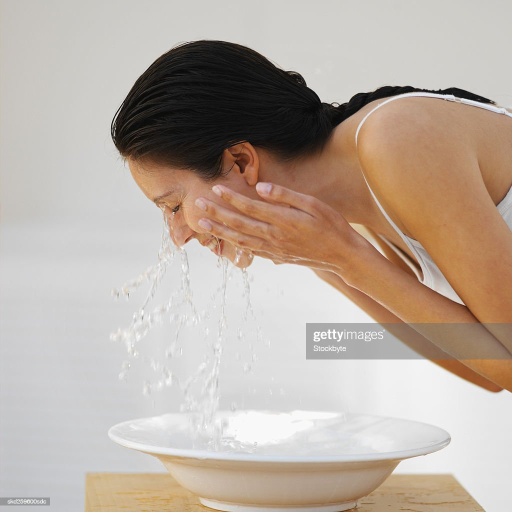 Side view of a woman washing her face : Stock Photo
