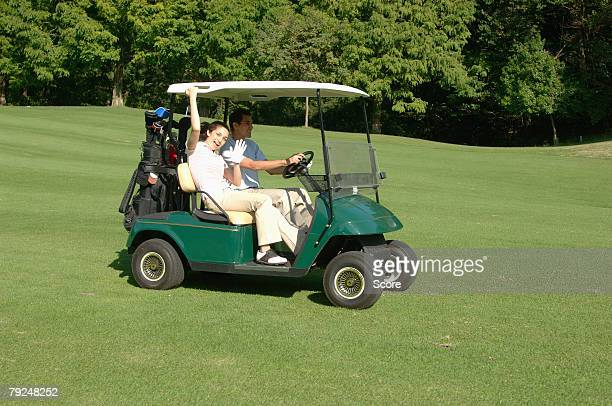 Side view of a woman waving whilst her partner drives a golf cart