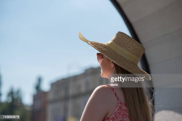 Side view of a woman wearing a straw hat